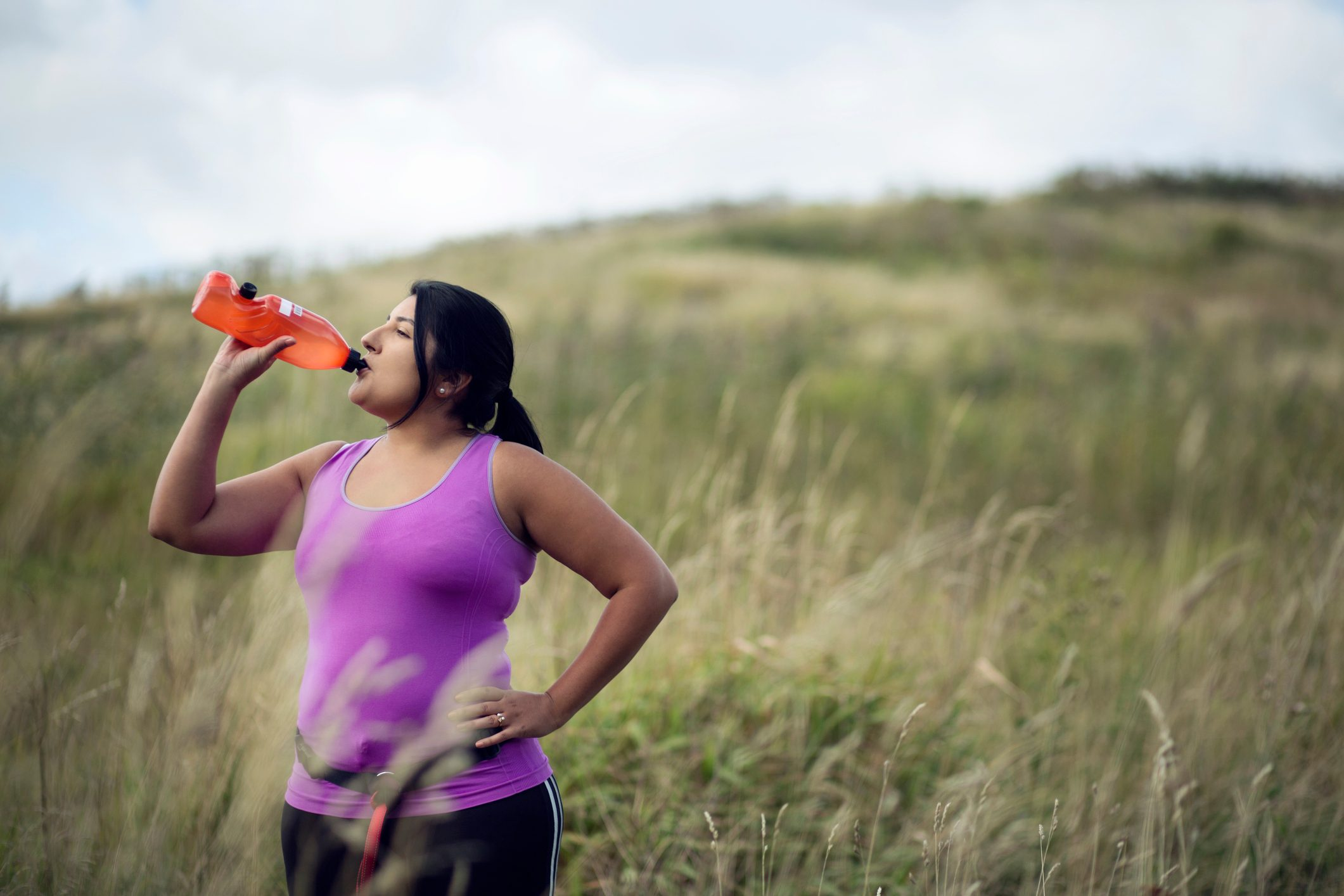 young woman drinking water while exercising outside