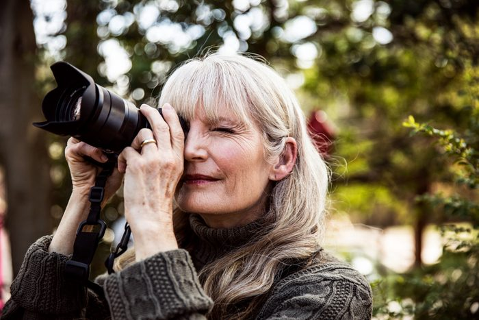 woman enjoying her photography hobby outside in nature