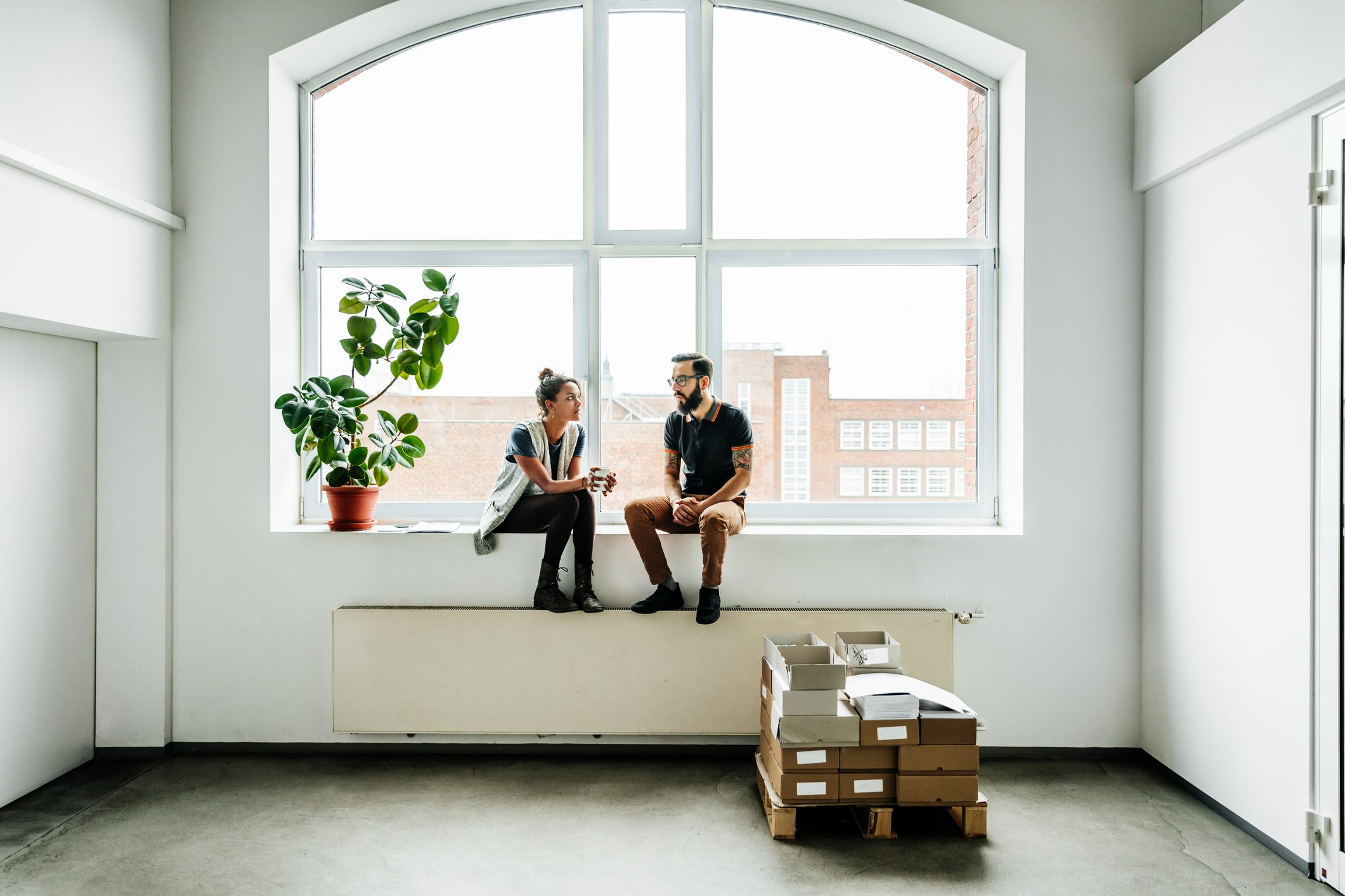 two people talking in empty room by the window