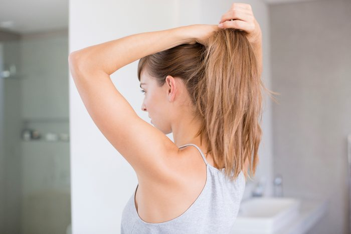 woman putting hair into ponytail