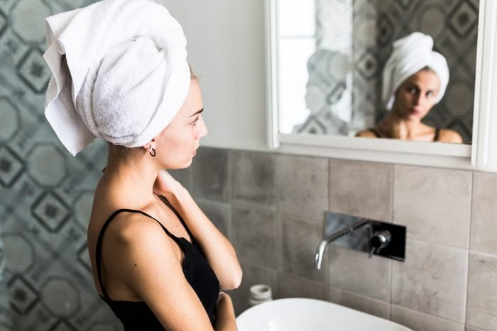 young woman with hair wrapped in towel looking at herself in the bathroom mirror