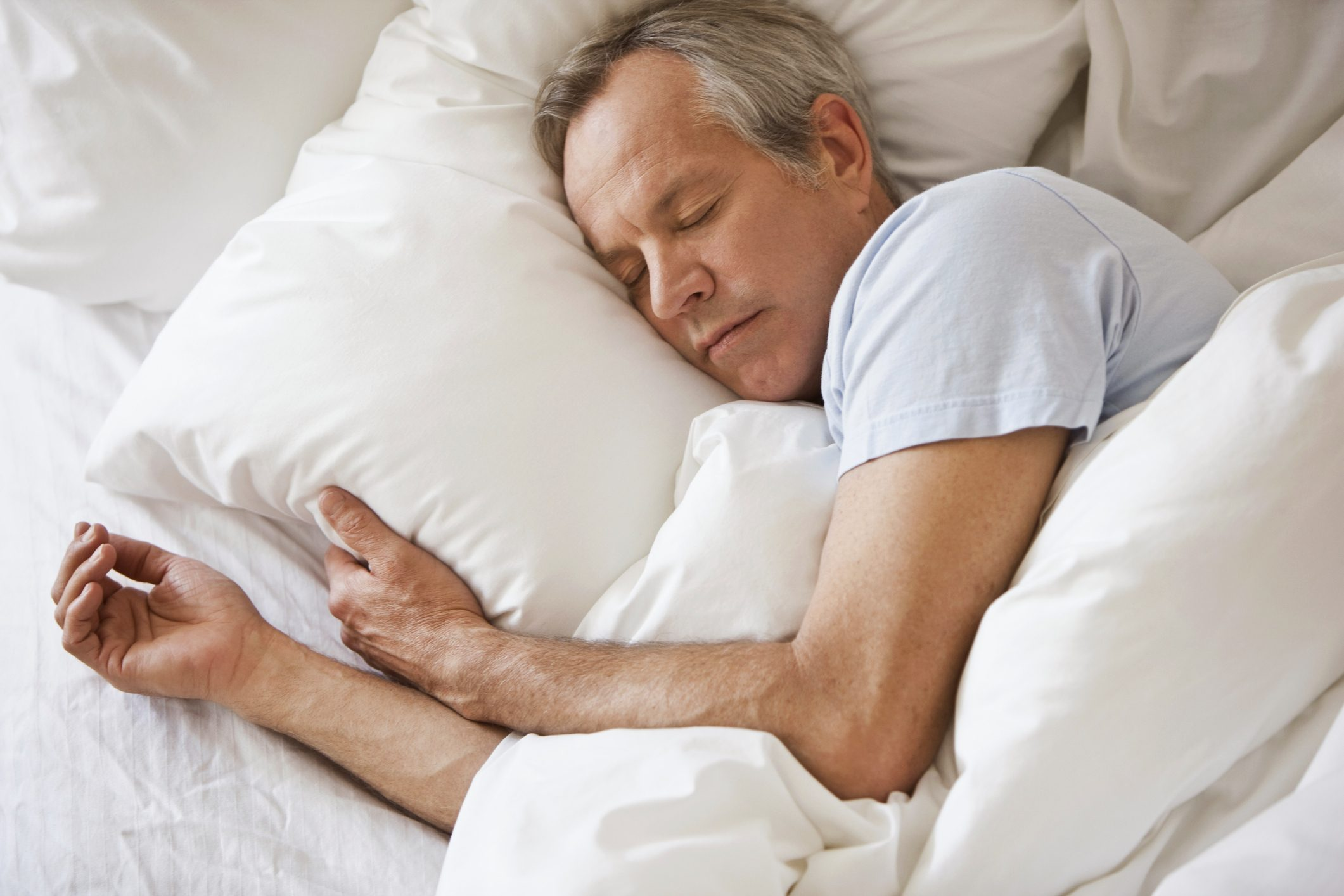 older man sleeping in bed