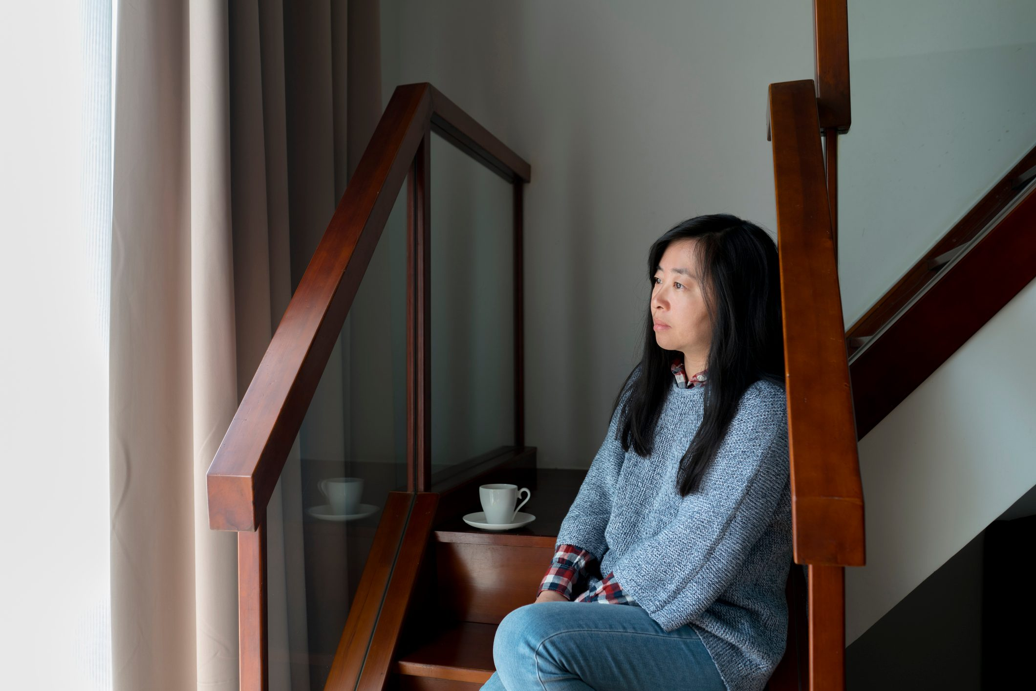 woman sitting at home looking out the window