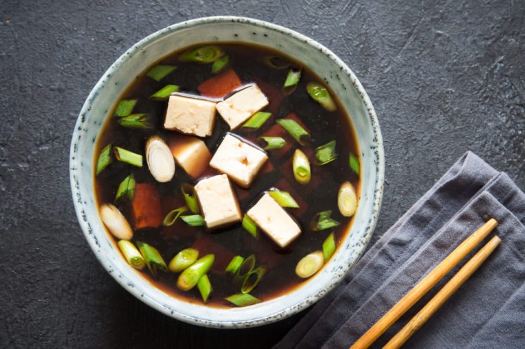 Japanese miso soup in ceramic bowl with tofu and green onions.
