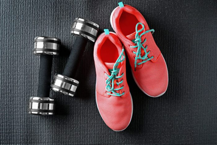 Pink running shoes and black dumbbells on dark background.