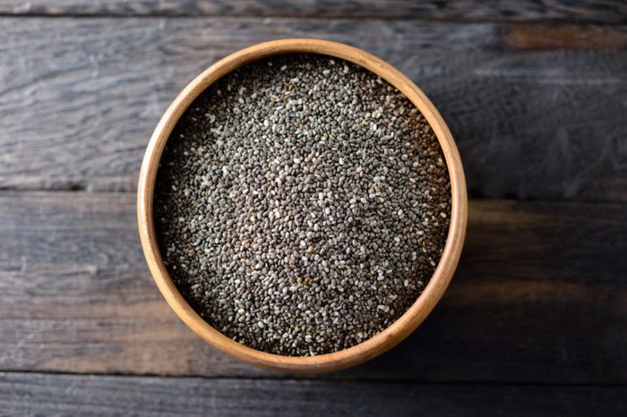 Bowl of chia seeds on a wooden surface.