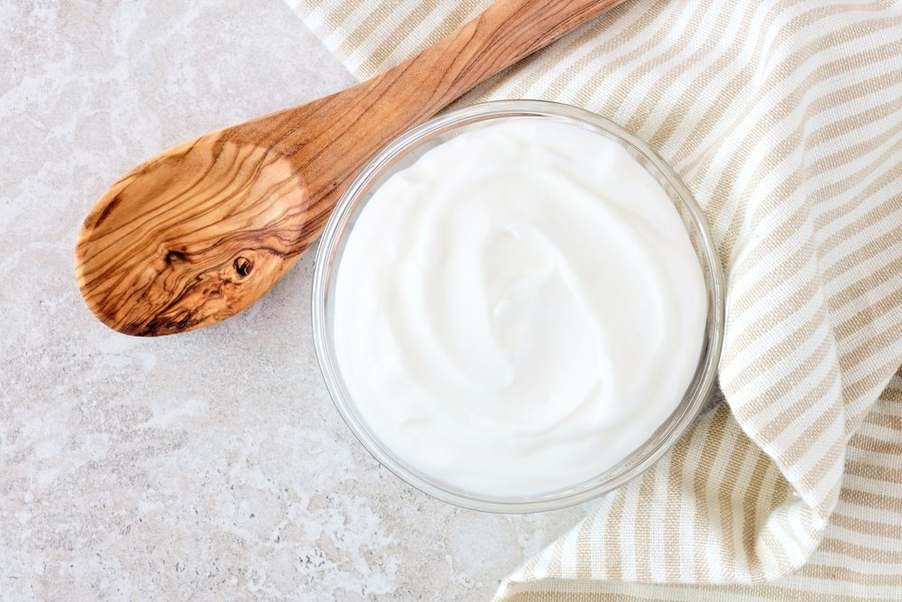 Greek yogurt in a glass bowl with wooden spoon