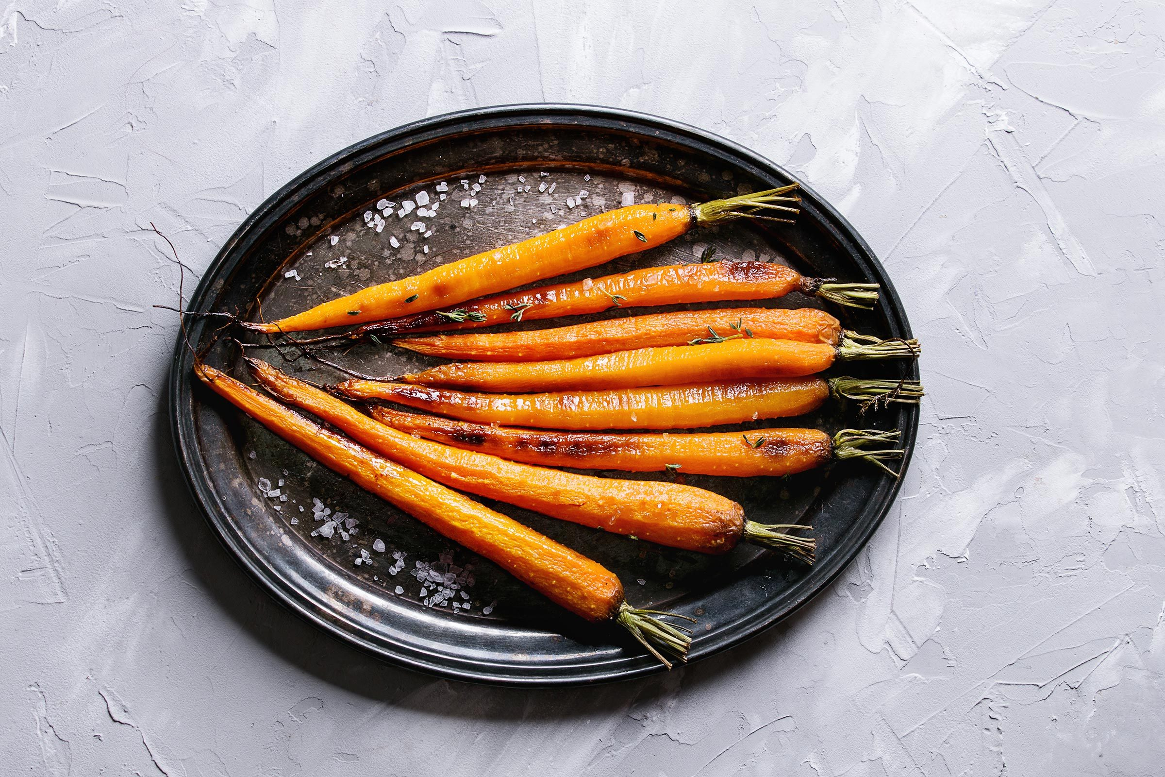 cooked, whole carrots on a black plate