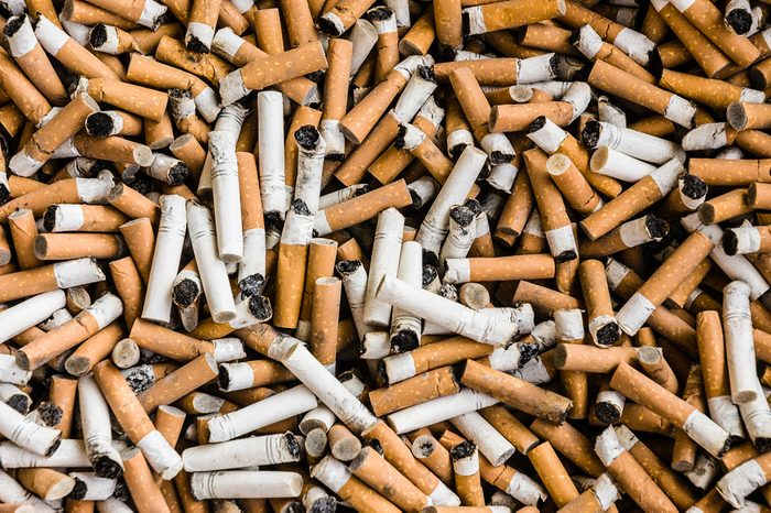 a lot of burnt cigarette butts with some ash