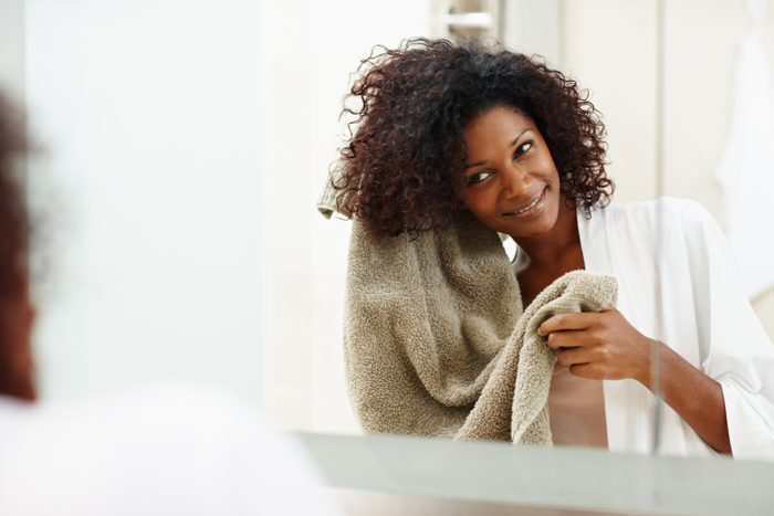 woman drying her hair with a towel after taking a shower