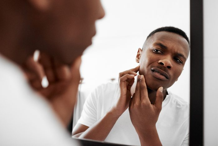 man looking at pimple in mirror
