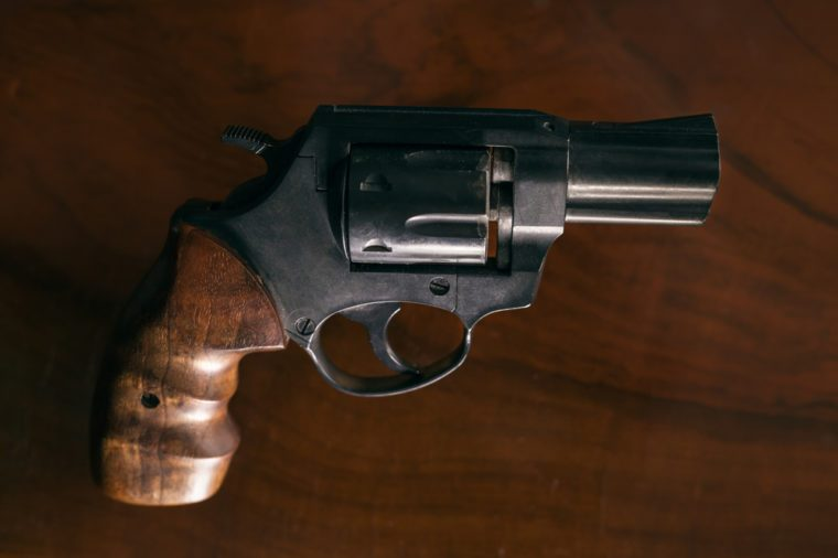 Revolver handgun over wooden background.