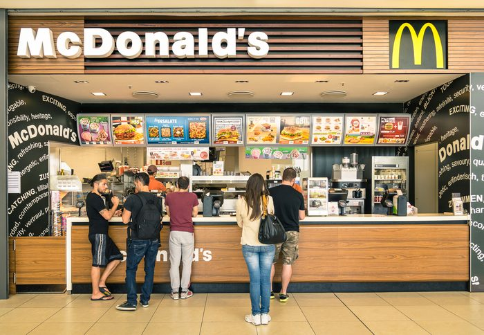 """RIMINI, ITALY - MAY 30, 2014: people waiting for the food service at Mc Donalds desk in the shopping mall """" Le Befane """" . The fast food company was founded in 1940 in San Bernardino, California."""