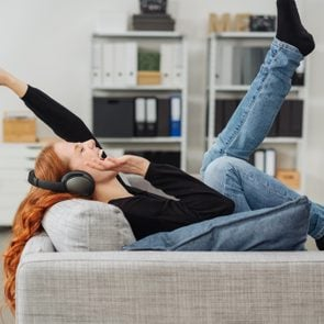 Exuberant young woman listening to music as she relaxes on a sofa laughing and kicking her legs and arms