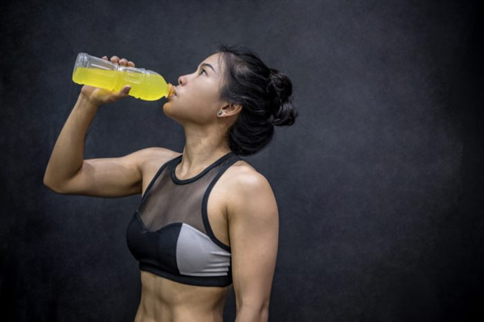 Young Asian athlete woman drinking sport drink or energy drink after exercise in fitness gym, healthy lifestyle concepts