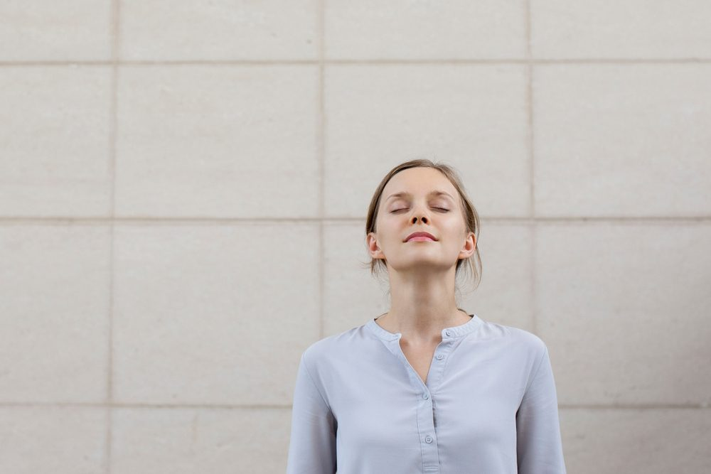 woman with eyes closed, relaxing against a wall