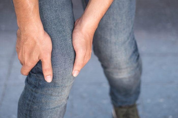 man holding leg thigh restless leg or knee pains