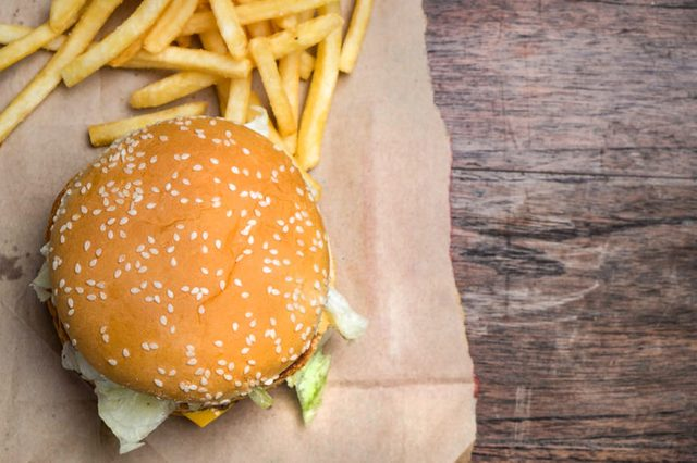 still life with fast food hamburger menu, french fries on wood desk