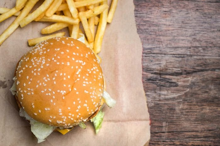 still life with fast food hamburger menu, french fries on wood desk