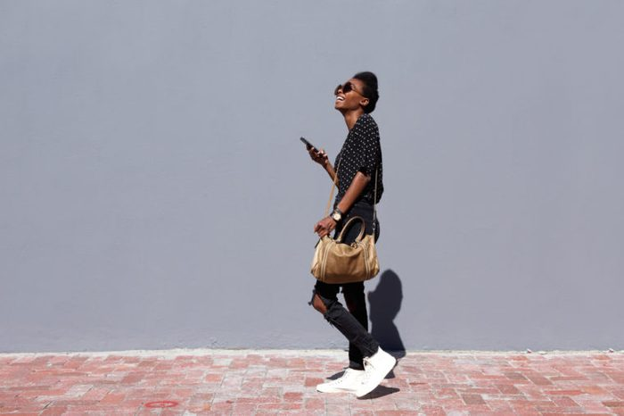 Full length side view portrait of smiling young black woman walking outdoors with mobile phone