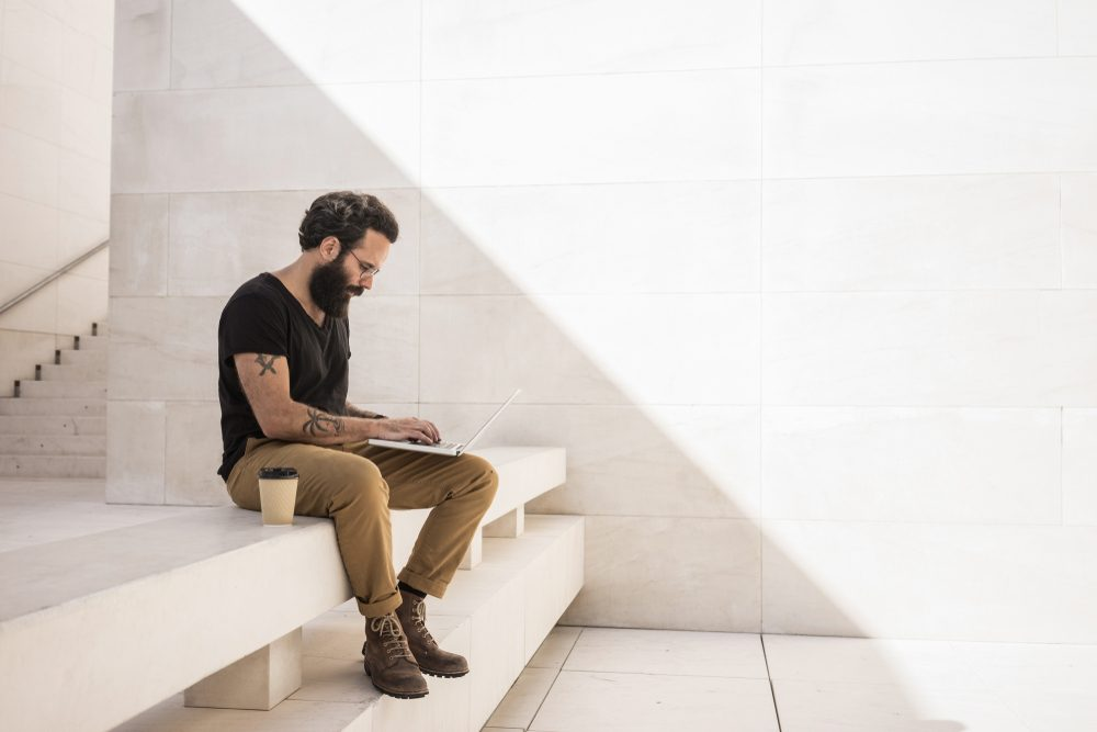 Bearded man sits on shade of minimalistic and geometric space with his computer working on project