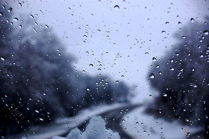 Dark clouds and snow storm viewed through car window