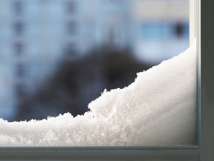 Modern residential window with snow landscape. Snowdrift on the window. Abstract winter backdrop.