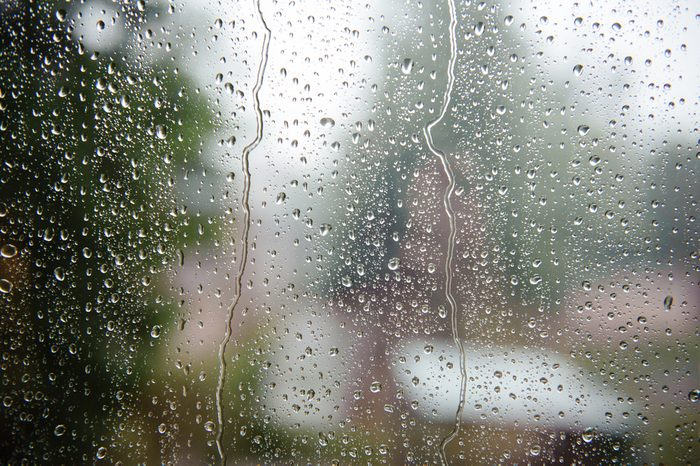 Water drops on the window on the background of an overcast sky