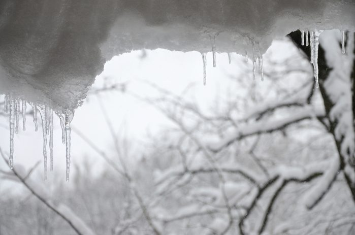 Several icicles are located above the blurred winter view from the window