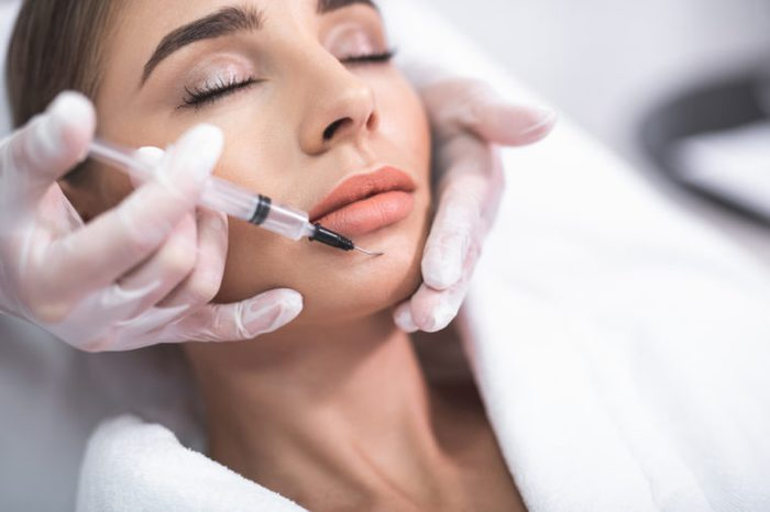 dentist injecting woman's chin with needle