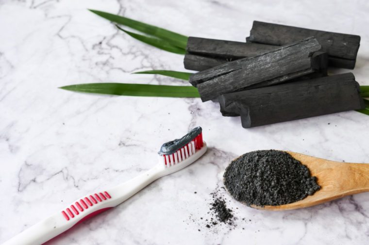 Toothbrush with charcoal toothpaste, spoon of charcoal powder, and charcoal