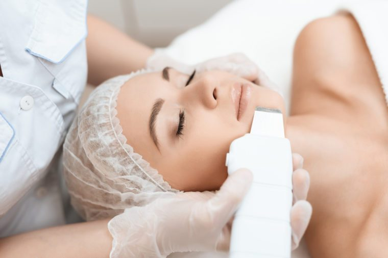 Esthetician or dermatologist applying medical device to woman's face