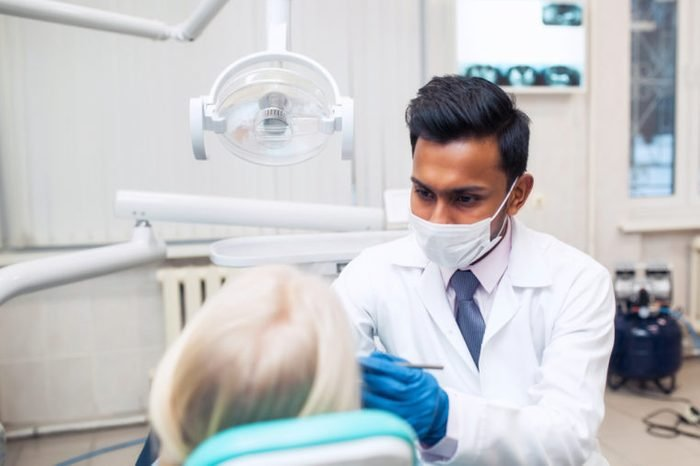 friendly dentist conversation patient open mouth during oral checkup with mirror near by, good healthcare in clinic office room concept. Trust in medicine treatment with professional handsome doctor.