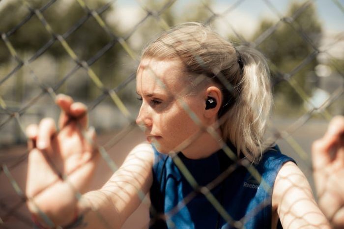 Fitness Woman Listening Music in Wireless Headphones, Doing Workout Exercises On Street. Beautiful Athletic Fit Girl Relaxing After Training. Sport style