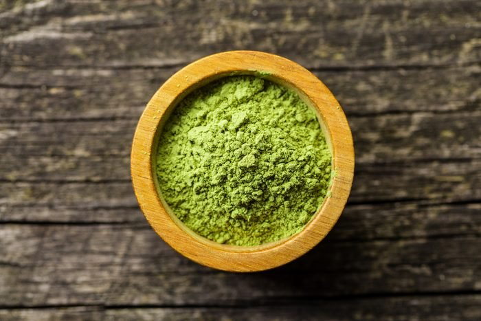 Green matcha tea powder in bowl. Top view.