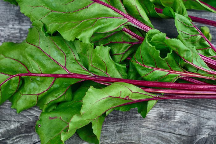 Wooden vintage background for design with fragment bright green, beautiful beet haulm. Top view