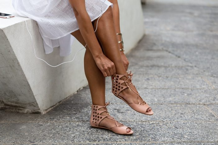 close up of hipster young tan skin woman wearing fashion shoe which feeling leg pain, ankle sore and sitting in the outdoor,healthy concept.