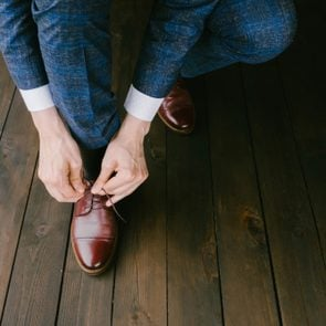 Man wearing a blue suit putting his brown shoes on. Hands and shoe close-up