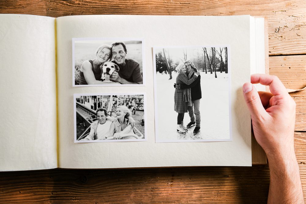 Hand holding photo album with pictures of senior couple. Studio