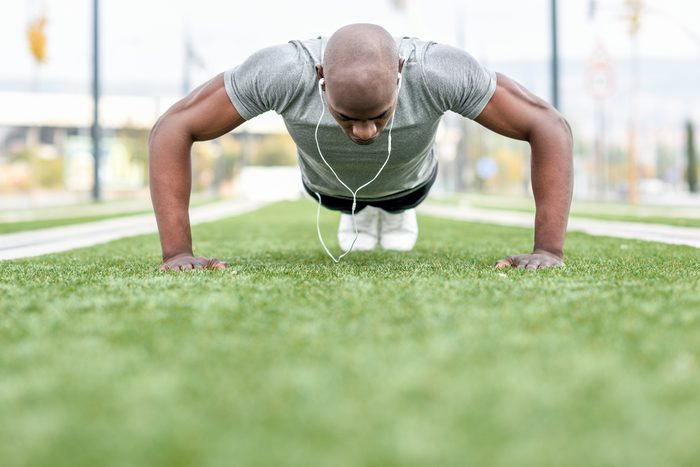 Man exercising push ups listening to music with headphones. Male model cross-training in urban background. African guy in his twenties doing workout outdoors in the street.