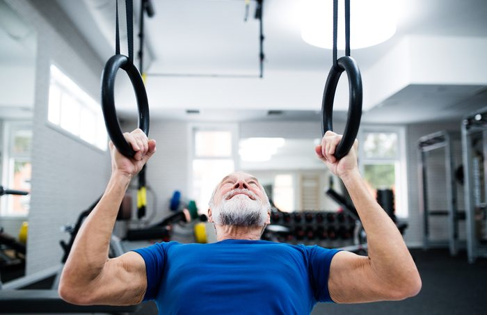 Man in gym working out on gymnastic rings