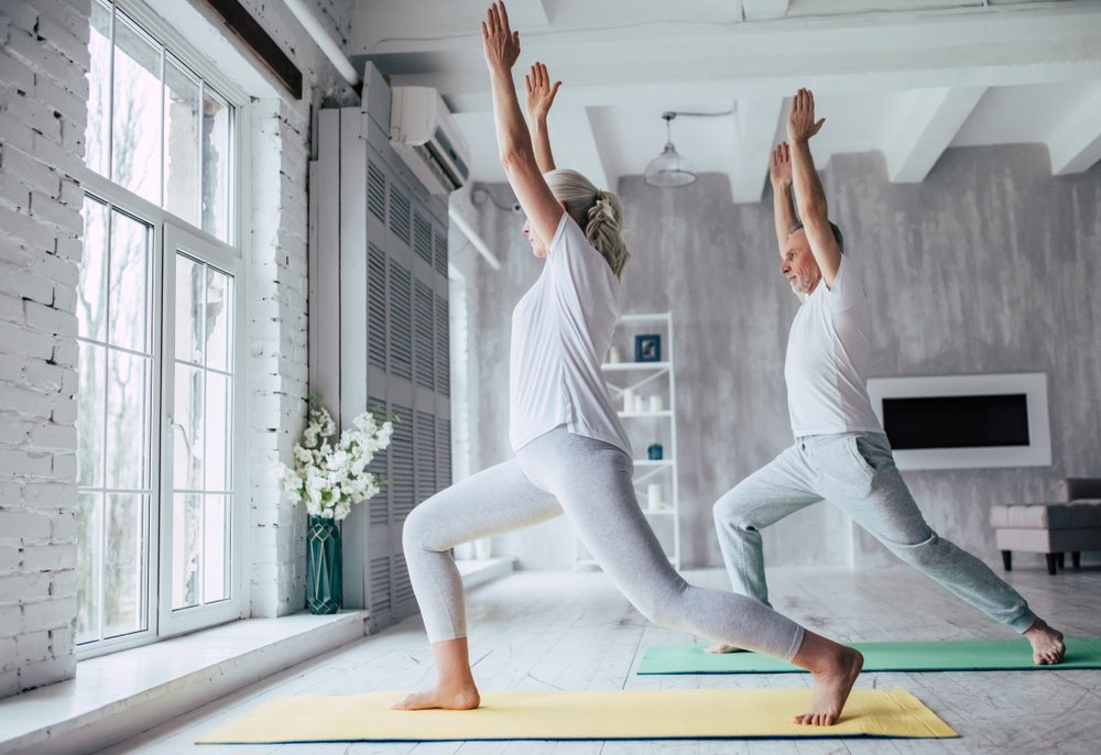 Couple is doing fitness training at home. Doing yoga together. Healthy lifestyle concept.