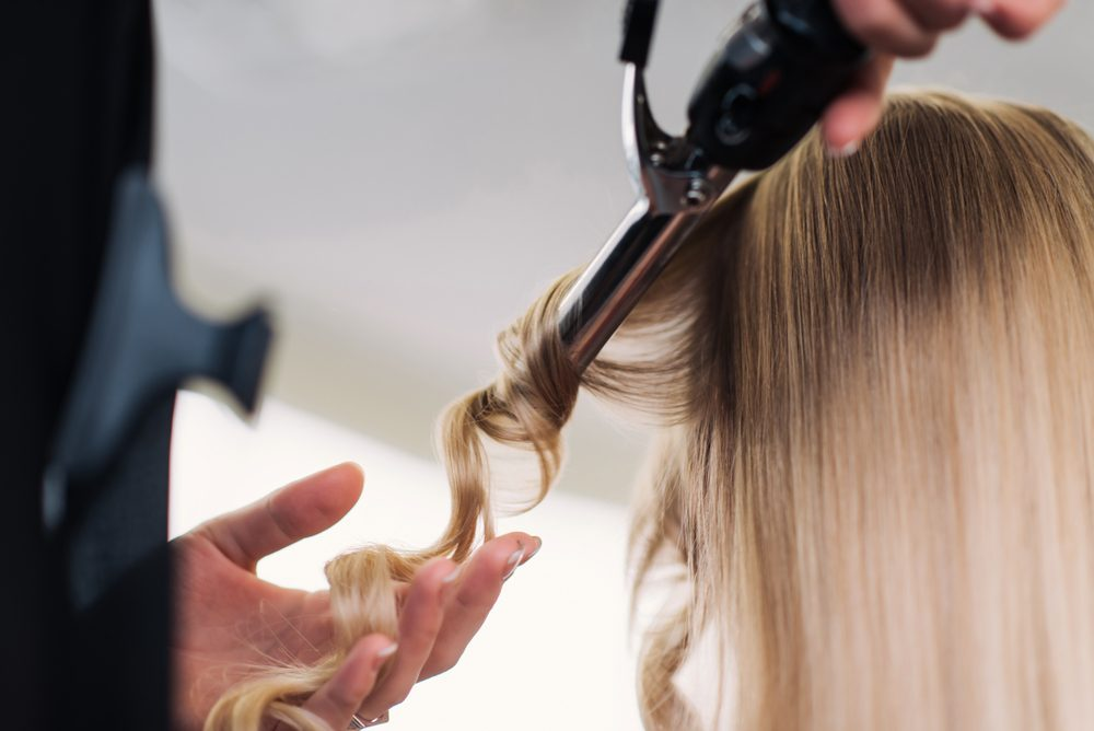 curling woman's hair giving a new hairstyle at hair salon close-up