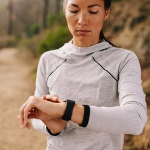 Asian female checking fitness progress on her smart watch. Fit young woman runner checking time on smart watch.