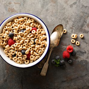 Healthy cold cereal with raspberry and blueberry in a bowl, quick breakfast or snack overhead shot