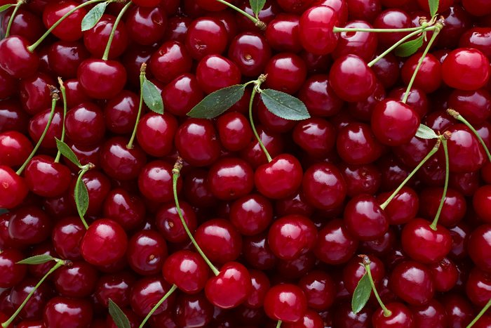 Close up of pile of ripe cherries with stalks and leaves.