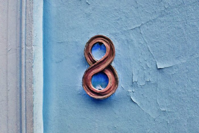 Number 8 house number on a blue wall.