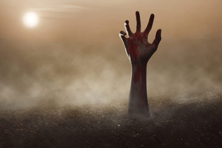 Zombie hand reaching out of the ground with a full moon.
