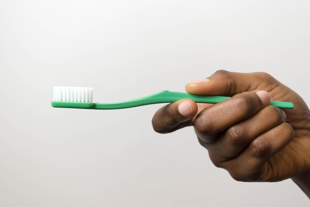 Clsoe up of green toothbrush in dark brown skin hand isolated on white background hand of African American young girl holding toothbrush.
