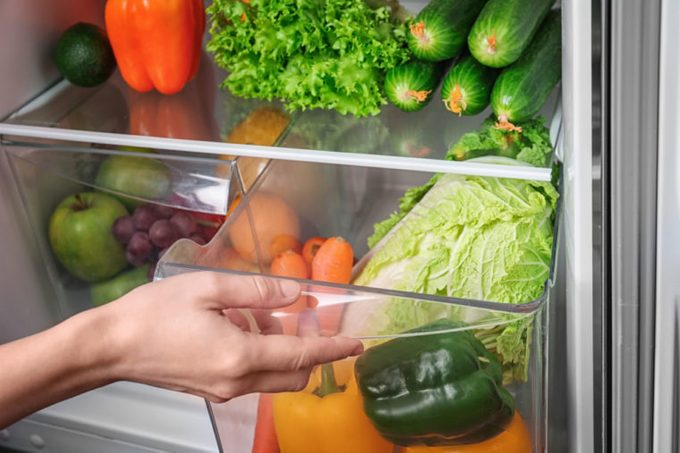Woman opening drawer of refrigerator with vegetables